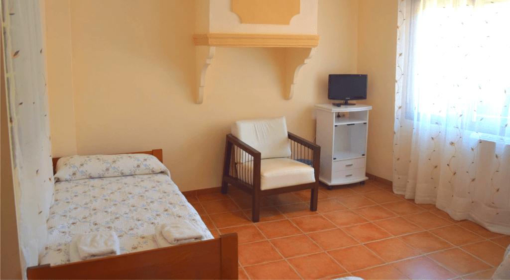 Tercera cama, sillón y televisión de la habitación familiar